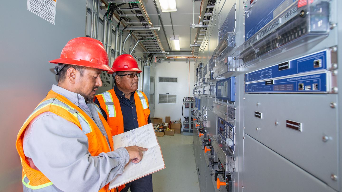 two men in a control house looking at equipment